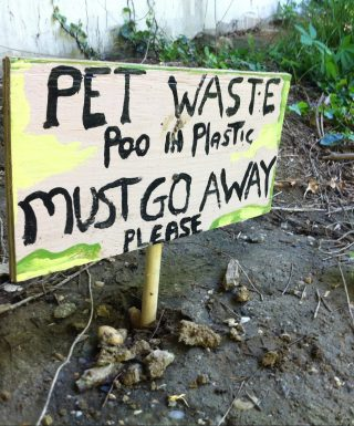 A sign misses one important detail: a poop bag at its base.