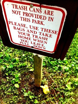 A poop bag punctuates a sign telling people to tend to their trash.